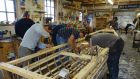 Boat-builders working on a currach in Meitheal Mara's workshop in Cork.
