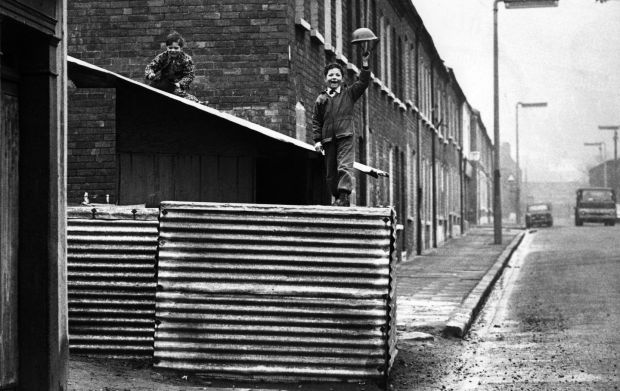 Troubles: boys play soldier in 1972 in an abandoned British army post north of the peace line separating Catholic and Protestant areas in Belfast. Photograph: Oliver Morris/Getty