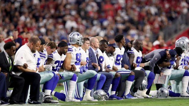Members of the Dallas Cowboys link arms and kneel during the National Anthem before the start of their meeting with the Arizona Cardinals last year. Photo: Christian Petersen/Getty Images