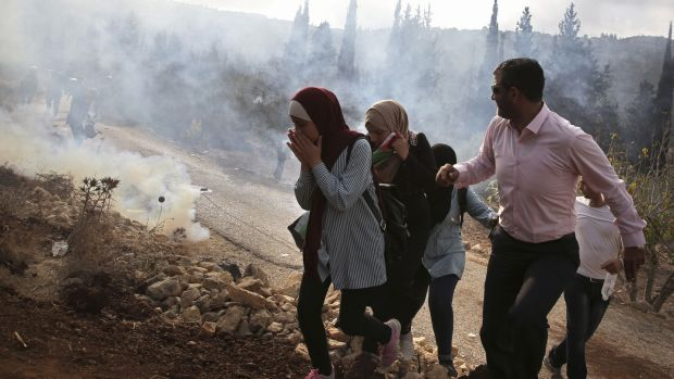 Palestinians run away from tear gas fired by Israeli forces during clashes over an Israeli order to shut down a Palestinian school in the town of as-Sawiyah, south of Nablus, in the occupied West Bank on October 15th. Photograph: Jaafar Ashtiyeh /AFP/Getty Images