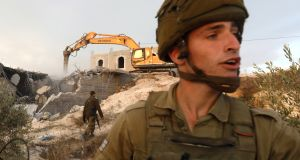 Israei soldiers at the scene as a  bulldozer demolishes a Palestinian house in Yatta village, south of the city of Hebron, on October 17th.   Israeli adminstrative control bans Palestinians from erecting buildings and infrastructure in Area C of the West Bank. Photograph: Abed al-Hashlamoun/EPA
