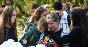 Teenagers mourn victims of the gun and nail-bomb attack at a vocational school in Kerch, Crimea. Photograph: Stringer/EPA