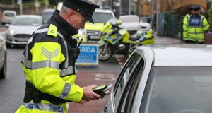A Garda stops a motorist at a checkpoint. File photograph: Colin Keegan/Collins