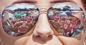 A group of revellers reflected in a womans sunglasses as crowds arrive for the Electric Picnic festival in Stradbally, County Laois. Photograph: Niall Carson/PA