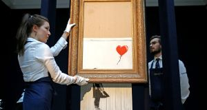 Staff from Sotheby's auctioneers reposition Banksy's Love is in the Bin, which is now half-shredded, in London. Photograph: Henry Nicholls/Reuters