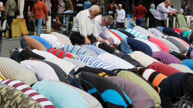 Men say Friday prayers on a street outside al-Husainy mosque in Amman. Photograph: Muhammad Hamed/Reuters