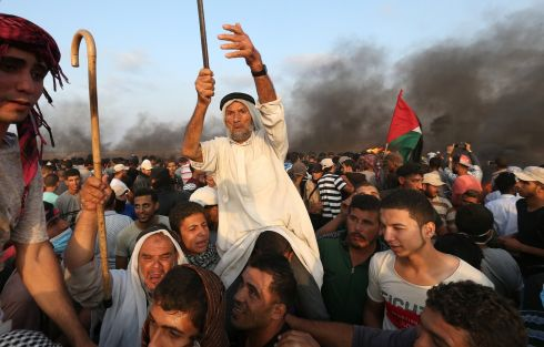 Palestinian demonstrators gather at the Israel-Gaza border fence during a protest calling for lifting the Israeli blockade on Gaza and demanding the right to return to their homeland, in the southern Gaza Strip. Photograph: Ibraheem Abu Mustafa/Reuters