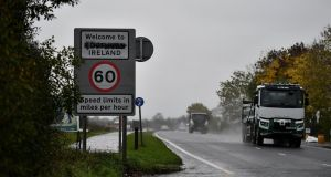 "Traffic moves by a defaced ""Welcome to Northern Ireland"" on the Border in Co Derry, earlier this month. Photograph:  Charles McQuillan/Getty Images"