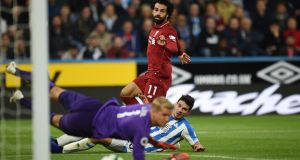 Liverpool's  Mohamed Salah steers his shot  past Huddersfield Town's  defender Christopher Schindler and   goalkeeper Jonas Lossl to score the winner at  the John Smith's stadium in Huddersfield. Photograph: Oli Scarff/AFP/Getty