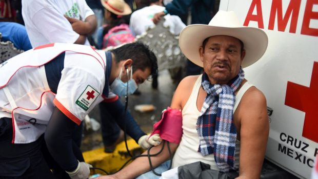 A paramedic checks the blood pressure of a migrant taking part in a caravan heading to the US, at the main square in Tapachula. Photograph: Johan Ordonez/AFP/Getty Images