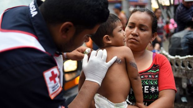 A paramedic attends a Honduran child migrant taking part in a caravan heading to the US, at the main square in Tapachula, Chiapas state, Mexico on Sunday. Photograph: Johan Ordonez/AFP/Getty Images