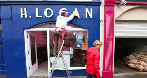 Butcher Hugh Logan shines up the shop's name on Main Street, Mohill, Co Leitrim. Photograph:  Brian Farrell