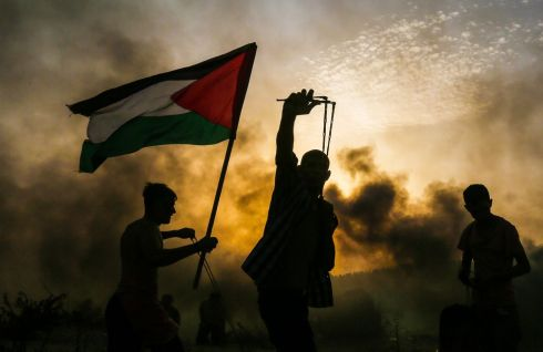 SMOKE AND SLINGSHOTS: A protester holds up a Palestinian national flag while another uses a slingshot to fire a stone towards Israeli forces during a demonstration on the beach near the maritime border with Israel, in the northern Gaza Strip. Photogrpah: Mahmud Hams/AFP/Getty Images