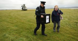 Garda Sgt John Gallagher and presiding officer Carmel McBride deliver a ballot box to Inishbofin island, off Co Galway, for the Irish presidential election and referendum on blasphemy. Photograph: Niall Carson/PA Wire