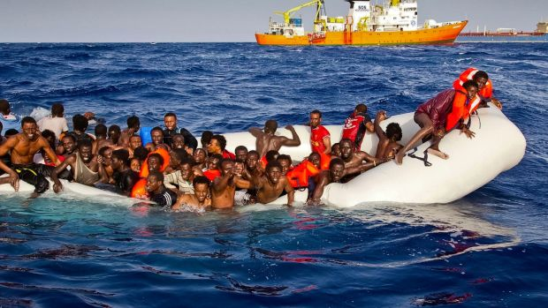 Migrants on a dinghy are approached by the Aquarius off the coast of the Italian island of Lampedusa. Photograph: Patrick Bar/SOS Mediterranee via AP