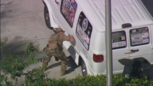 A law enforcement officer checks a van seized during an investigation into a series of parcel bombs, in Plantation, Florida. Image: via Reuters.