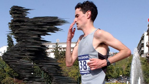 "Ian O'Riordan from Ireland passes by the statue ""The Runner"" during the Athens Classic Marathon in 2003. Photograph: Orestis Panagioutou/EPA"