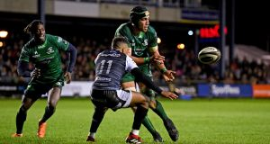 Ultan Dillane of Connacht gets his pass away as Keelan Giles of Ospreys closes in for the tackle in the Guinness Pro 14 game at  Morganstone Brewery Field in  Bridgend. Photograph: Alex Davidson/Inpho