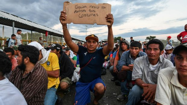 "A Honduran migrant taking part in the caravan holds up a sign reading ""Thank you Mexico for opening your hearts to us"", while he waits to cross the border from Ciudad Tecun Uman in Guatemala, to Ciudad Hidalgo, Mexico earlier this week. Photograph: Orlando Sierra/AFP/Getty Images"