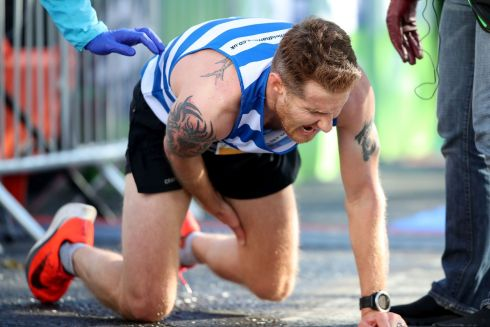 Stephen Wylie cramps up after crossing the finish line. Photograph: Bryan Keane/INPHO