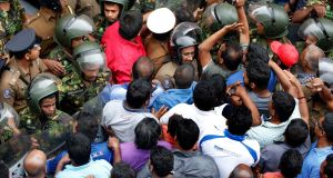 A crowd clashes   with Sri Lankan police  outside the state-run  Ceylon Petroleum Corporation head office where a shooting took place. Photograph:  M.A.Pushpa Kumara/EPA