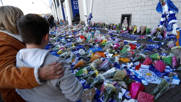 Leicester City football fans pay their respects outside the King Power Stadium, after the helicopter of the club's owner, Thai businessman Vichai Srivaddhanaprabha, crashed when leaving the ground on Saturday evening. Photograph: Peter Nicholls/Reuters