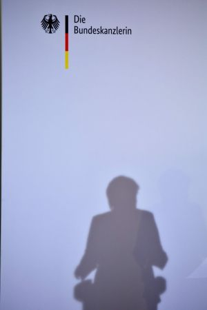 CAST A SHADOW: German chancellor Angela Merkel's shadow is cast on a wall as she gives a speech in Berlin after announcing she will quit her position. Photograph: Tobias Schwarz/AFP/Getty Images