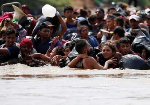 MIGRATION CRISIS: Central American migrants walk through the Suchiate river in their bid to reach the US. Photograph: Carlos Garcia Rawlins/Reuters