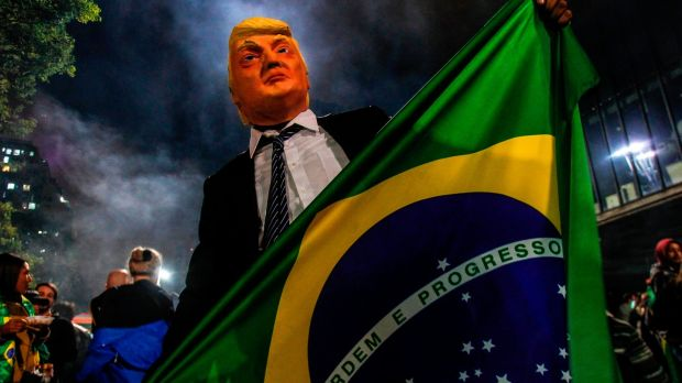 A Bolsonaro supporter wears a mask of US president Donald Trump as he celebrates after Bolsonaro won. Photograph: Miguel Schincariol/AFP/Getty Images