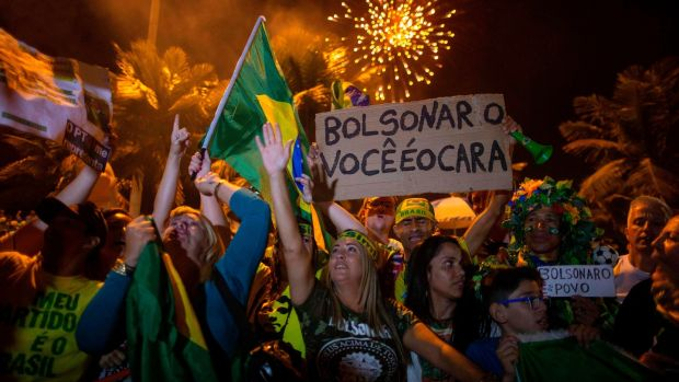 Supporters of Jair Bolsonaro, celebrate in front of his house in Rio de Janeiro. Photograph: Mauro Pimentel / AFP