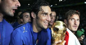 Italian forward Vincenzo Iaquinta (left), Luca Toni (centre) and Francesco Totti (right) pose with the 2006 World Cup trophy. Photo: Pascal Pavani/Getty Images