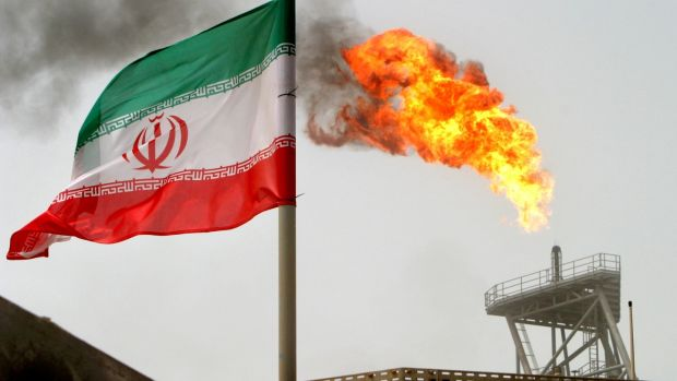 A gas flare on an oil production platform in the Soroush oil fields alongside an Iranian flag in the Persian Gulf, Iran. File photograph: Raheb Homavandi/Reuters