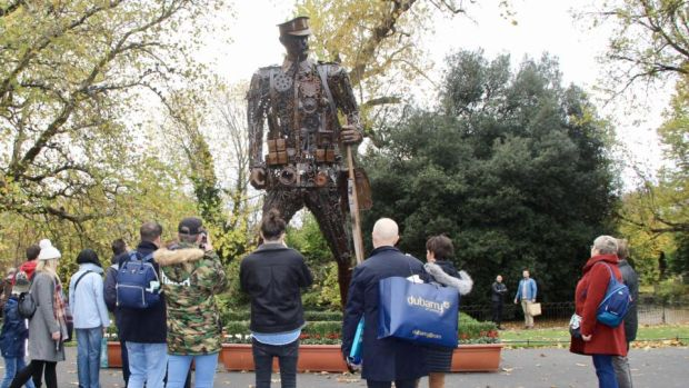 "People take in the 'Haunting Soldier' at St Stephen's Green, Dublin, on Saturday. Sabina Purcell, who organised the work's installation in Dublin, said: ""There are hordes of people around it taking photos. I'm so moved by the respect being shown to it by members of the public."" Photograph: Ronan McGreevy"