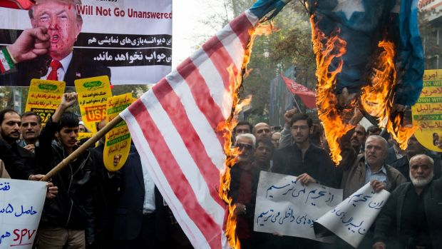 Protesters hold a burning American flag during a demonstration on the anniversary of the US embassy seizure in Tehran. Photograph: Ali Mohammadi/Bloomberg