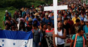 "Migrants, part of a ""caravan"" travelling towards the United States,  carry a Honduras flag and a cross in Pijijiapan, Mexico, on Sunday. Photograph: Carlos Garcia Rawlins/Reuters"