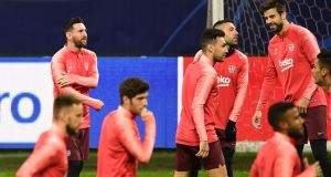 Lionel Messi holds his injured arm during Barcelona's training session at the San Siro stadium ahead of Tuesday night's Champions League game against Inter Milan. Photograph:   Miguel Medina/AFP/Getty Images