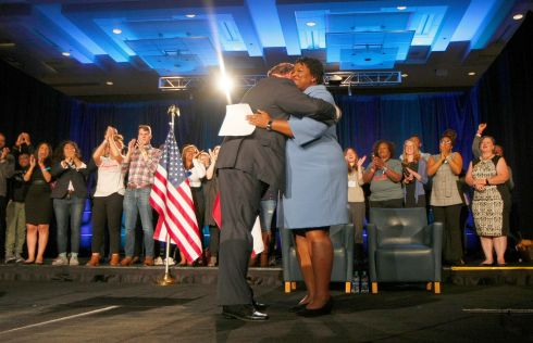 Chairman of the Democratic Party of Georgia DuBose Porter (C-L) hugs Democratic gubernatorial candidate Stacey Abrams (C-R) as she arrives to speak to supporters - and refuses to concede - in Atlanta Georgia. Photograph:  EPA/TAMI CHAPPELL