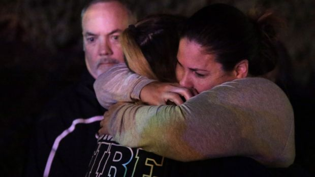 A woman who fled the Borderline Bar and Grill where a gunman injured 11 people is hugged by relatives in Thousand Oaks, California. Photograph: Mike Nelson/EPA