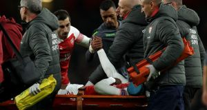 Sporting Lisbon's Nani grasps the hand of the  injured Danny Welbeck after  the Arsenal striker was stretchered off with  a serious leg injury during the Europa League game at Emirates stadium. Photograph: Richard Heathcote/Getty Images