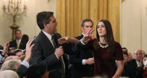 A White House intern reaches for and tries to take away the microphone held by CNN correspondent Jim Acosta as he questions US president Donald Trump during a news conference at the White House on Wednesday. Photograph: Jonathan Ernst/Reuters