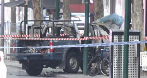A burnt out vehicle is seen on Bourke Street in Melbourne. Media reports say a man set a vehicle alight and stabbed two people before being shot by police. Photograph: EPA