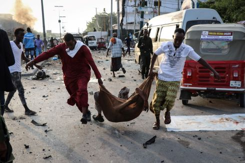 SOMALIA ATTACKS: People rescue a wounded person following three suicide bomb car attacks in Mogadishu, Somalia. Photograph: Abdirazak Hussein Farah/AFP/Getty Images