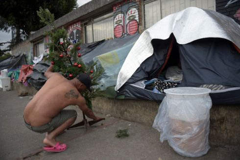 VENEZUELA CRISIS: A Venezuelan migrant holds a Christmas tree at an improvised camp near a bus terminal in Bogota, Colombia. Photograph: Raul Arboleda/AFP/Getty Images