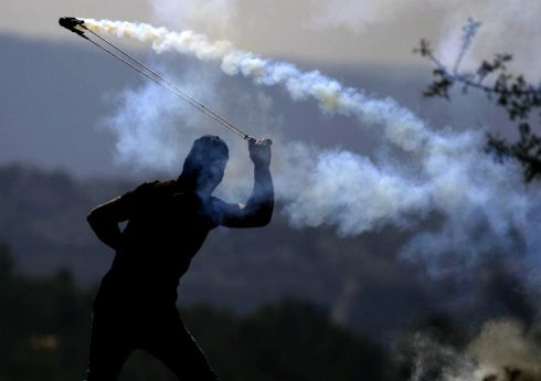 ISRAEL-PALESTINE CONFLICT: A Palestinian throws a tear gas canister towards Israeli soldiers during a rally against Israeli land seizures, in the West Bank. Photograph: Abbas Momani/AFP/Getty Images
