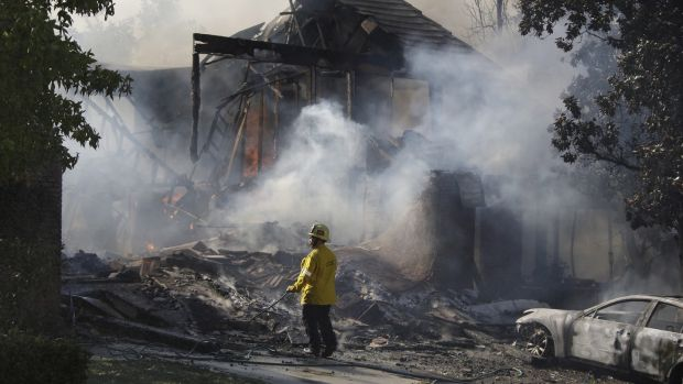 A firefighter inspects the smouldering ruins of a home destroyed in Agoura, California on November 9th, 2018. Photograph: Mike Nelson/EPA