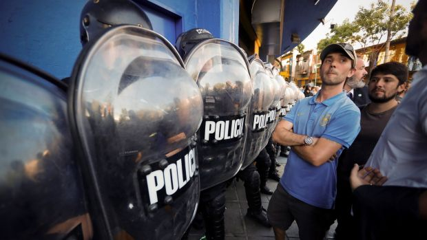 Policemen on guard as fans queue to buy tickets for the first match of the Copa Libertadores final. Photograph: Juan Ignacio Roncoroni/EPA