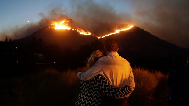 Roger Bloxberg and his wife Anne hug as they watch a wildfire on a hilltop near their home in West Hills, California. Photograph: Marcio Jose Sanchez/AP Photo