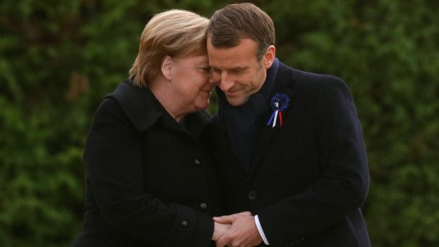French president Emmanuel Macron and German chancellor Angela Merkel hug after unveiling a plaque in the Clairiere of Rethondes during a commemoration ceremony for Armistice Day, 100 years after the end of the first World War, in Compiegne, France. Photograph: Philippe Wojazer/EPA