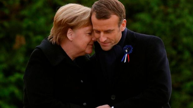 French president Emmanuel Macron and German Chancellor Angela Merkel hug after unveiling a plaque in a French-German ceremony in the clearing of Rethondes (the Glade of the Armistice) in Compiegne, northern France on Saturday. Photograph: Philippe Wojazer/Pool/AFP/Getty