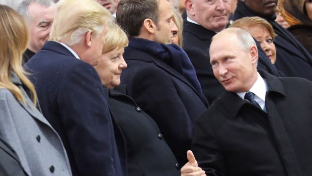 Russian president Vladimir Putin (R), talks with German Chancellor Angela Merkel (C) and US President Donald J. Trump as they attend the international ceremony for the Centenary of the WWI Armistice of 11 November 1918 at the Arc de Triomphe, in Paris. Photograph: Ludovic Marin/EPA